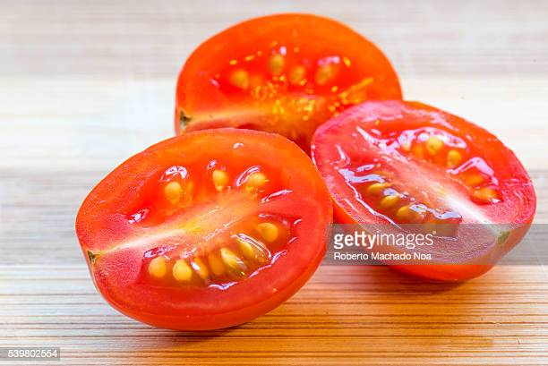 Delicious red cherry tomatoes cut in half Fruit resting on top of cutting board