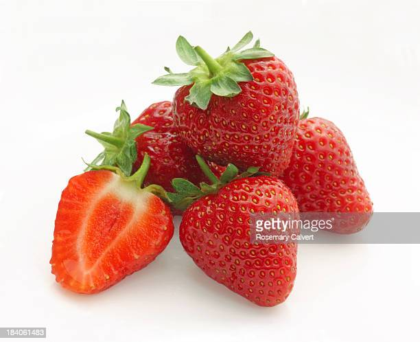 Delicious strawberries in pile, one cut through