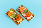 delicious summer sandwiches with cottage cheese with greens and vegetables on a blue background