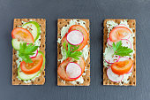 delicious summer sandwiches with cottage cheese with herbs and vegetables,sprinkle with flax seeds on a stone Board