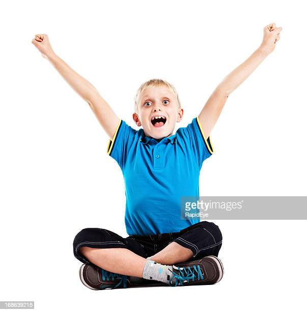 Delighted and elated little boy sitting cross legged