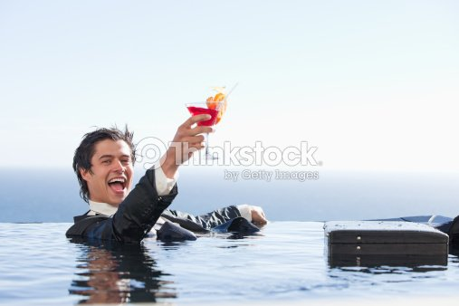 Delighted businessman relaxing in a swimming pool with a cocktail : Foto de stock