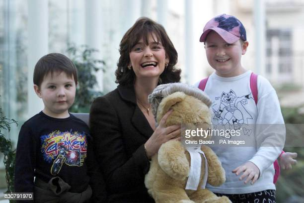 A delighted Cherie Booth wife of British Prime Minister Tony Blair receives a teddy bear today from Cory Moore aged 6 and Isobel Pearson Evans aged 8...