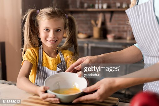 Delighted daughter holding the bowl with her mother : Stock Photo