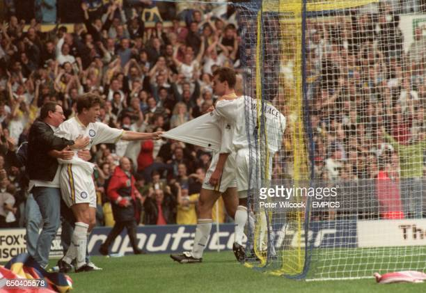 A delighted fan celebrates with Leeds United's Harry Kewell David Wetherall and Rod Wallace after Wetherall's goal