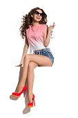 Happy beautiful young woman in pink top, jeans shorts and high heels sitting with legs crossed on the top of white banner. Full length studio shot isolated on white.