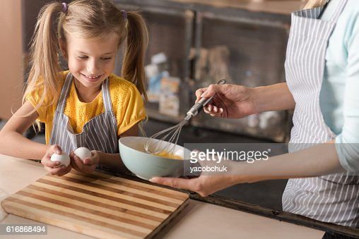Delighted girl helping her mother in the kitchen : Stock Photo