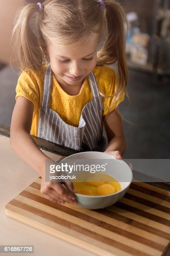 Delighted girl holding the bowl with broken eggs : Stock Photo