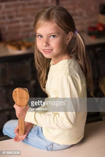 Delighted girl holding wooden spoon and sitting on the table : Stock Photo