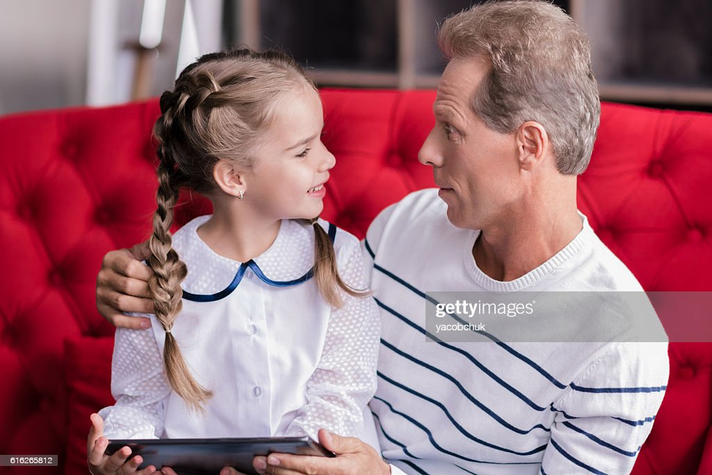 Delighted girl resting with her grandfather : Stock Photo