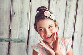Cheerful little girl with flowers in her hair posing in front of white background