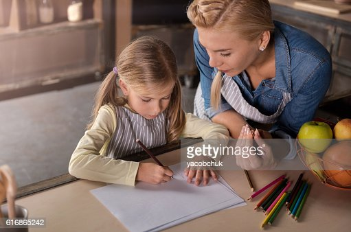 Delighted mother drawing with her daughter in the kitchen : Stock Photo