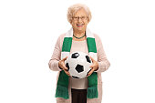 Delighted senior soccer fan with a scarf and a football isolated on white background