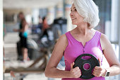 Happy fitness. Beautiful active woman turning head and smiling while exercising with plate in a gym.