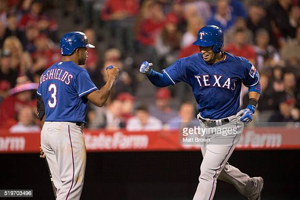 Delino DeShields and Robinson Chirinos of the Texas Rangers fist bump as Chirinos crosses home plate after hitting a solo home run during the third...