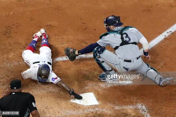 Delino DeShields of the Texas Rangers beats the tag at home by Mike Zunino of the Seattle Mariners as he scores on a double by ShinSoo Choo in the...