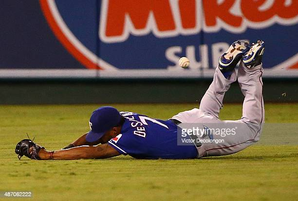 Delino DeShields of the Texas Rangers can't make the diving catch on a fly ball to shallow center field hit by Kole Calhoun of the Los Angeles Angels...