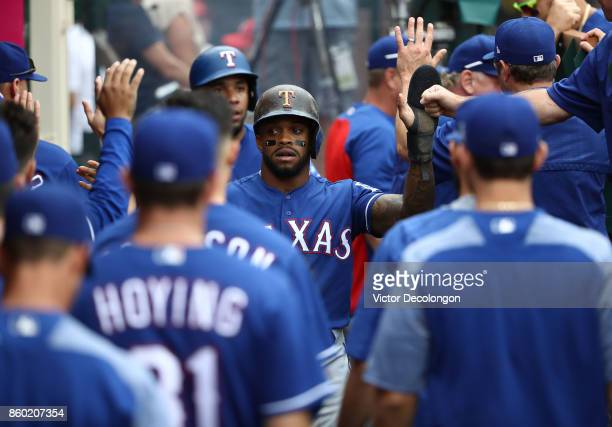 Delino DeShields of the Texas Rangers celebrates in the dugout with teammates after scoring in the first inning during the MLB game against the Los...
