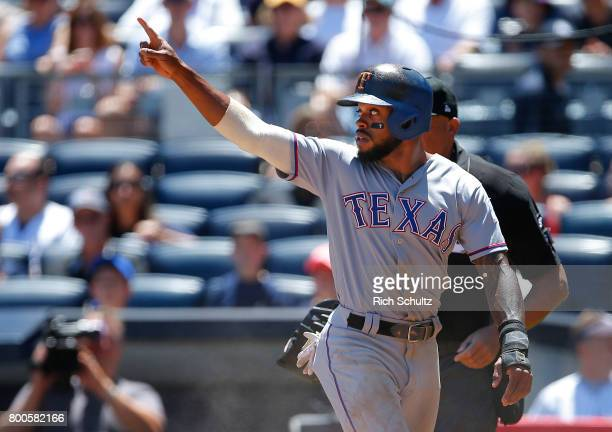 Delino DeShields of the Texas Rangers gestures to Elvis Andrus after scoring on a single by Elvis Andrus during the first inning of a game against...