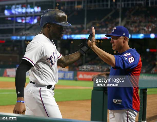 Delino DeShields of the Texas Rangers high fives manager Jeff Banister of the Texas Rangers after scoring in the first inning of a baseball game...