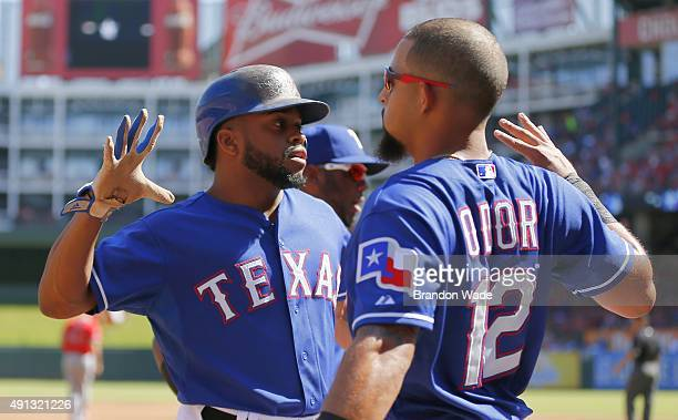 Delino DeShields of the Texas Rangers left is congratulated by Rougned Odor after scoring a run during the first inning of a baseball game against...