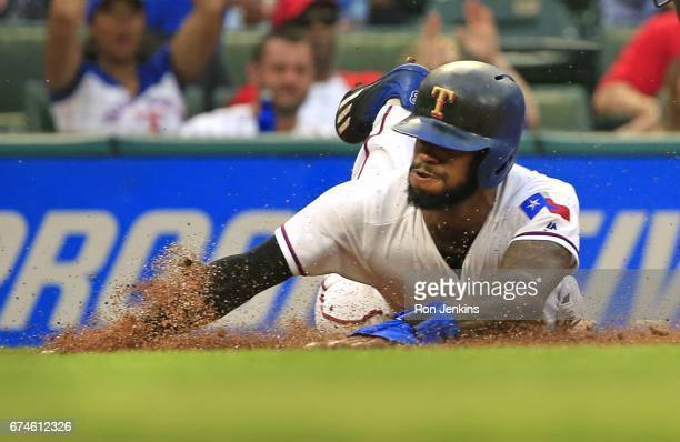 Delino DeShields of the Texas Rangers slides head first across the plate to score a run against the Los Angeles Angels of Anaheim in the first inning...