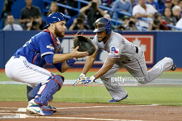Delino DeShields of the Texas Rangers slides into home safely ahead of the tag by Russell Martin of the Toronto Blue Jays in the first inning against...