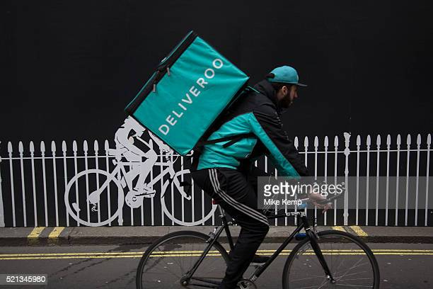 Deliveroo cycle courier with his large back box interacts with a stencilled cyclist while out delivering in London England United Kingdom