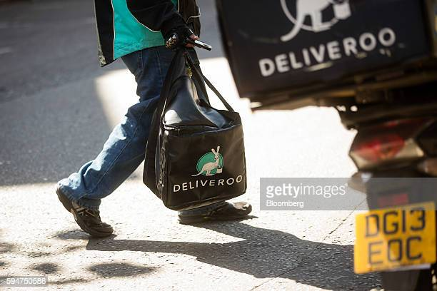 A Deliveroo operated by Roofoods Ltd food delivery driver carries an insulated food bag to his scooter parked on a street in London UK on Monday Aug...