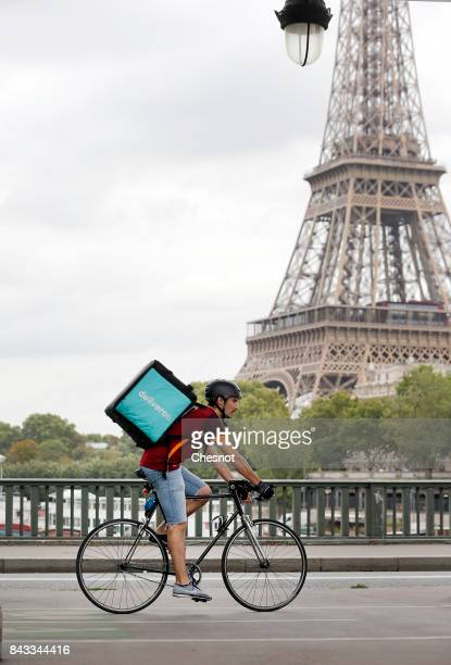 Deliveroo rider cycles past the Eiffel tower on a bicycle track on September 6 2017 in Paris France Mayor of Paris Anne Hidalgo launched the 'Plan...