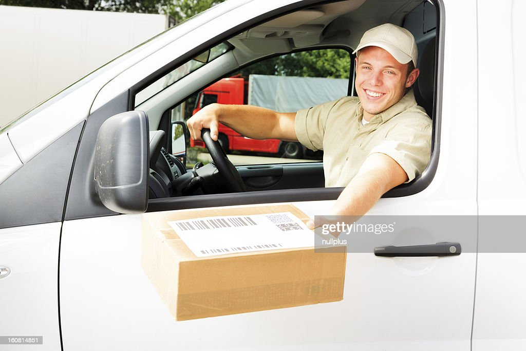 delivery boy handing you a parcel : Stock Photo