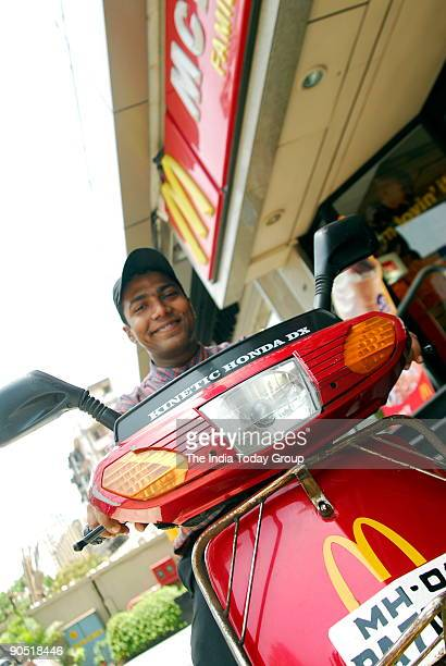 Delivery Boy poses outside Mc Donalds Restaurant with Kinetic Honda Scooter Vehicle used to deliver the food in Mumbai India