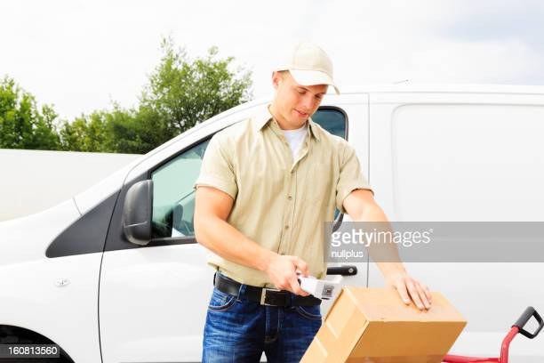 delivery boy standing next to his van