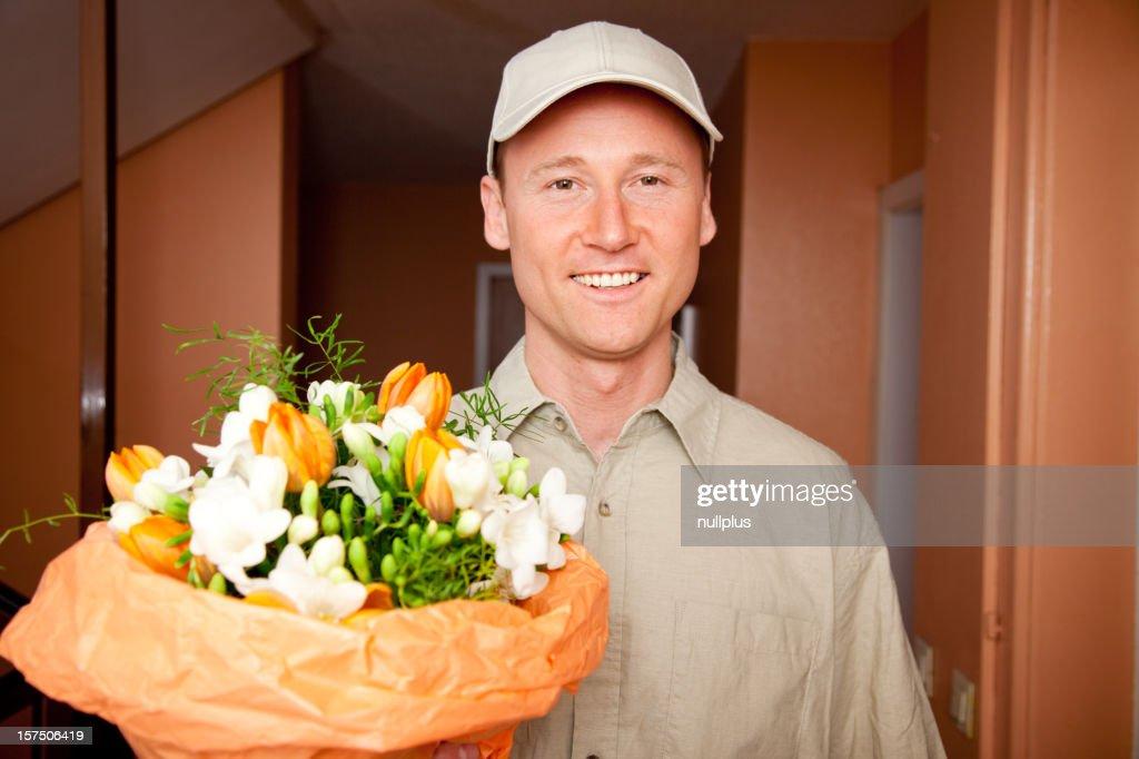 Lieferung Junge mit Blumen auf dem Zimmer. : Stock-Foto