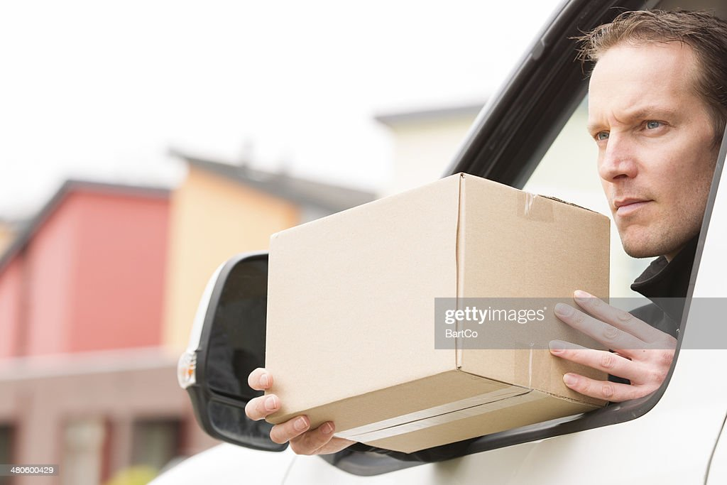 Delivery courier in a van delivering package : Stock Photo