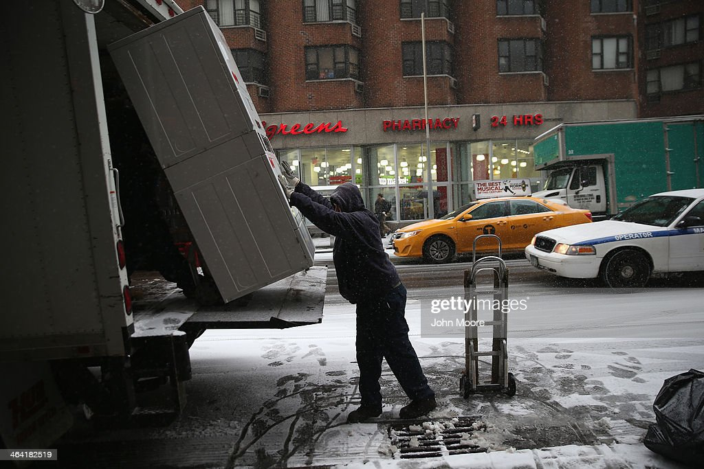 A delivery crew loads appliances onto a truck during a snowstorm on January 21, 2014 in New York City. Areas of the Northeast are predicted to receive up to a foot of snow in what may be the biggest snowfall of the season so far.