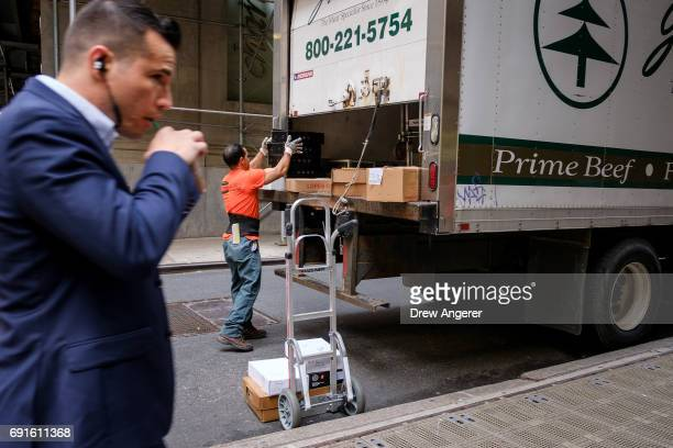A delivery driver unloads packages from the the back of his truck June 2 2017 in New York City While US unemployment has hit it lowest level since...