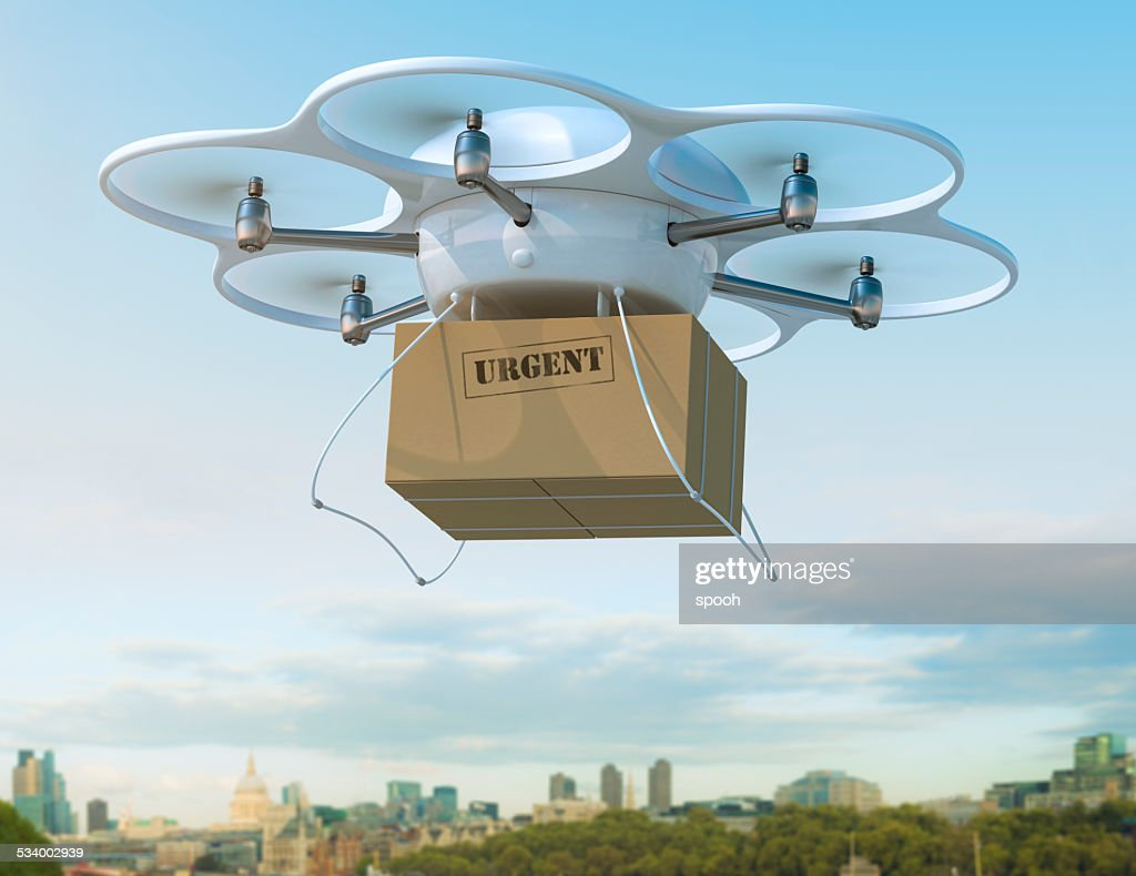 Delivery drone carrying urgent shipment box in a city. : Stock Photo
