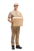 Full length portrait of a delivery guy holding a package isolated on white background
