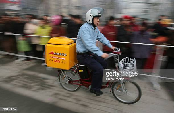 A delivery guy rides his bicycle during an opening ceremony of Pizza Hut Delivery on January 18 2007 in Nanjing of Jiangsu Province China After years...