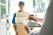 delivery, mail, people and shipping concept.Young woman sign in digital mobile phone after receiving parcel from courier at home.