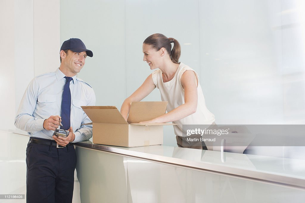 Delivery man bringing box to receptionist : Stock Photo