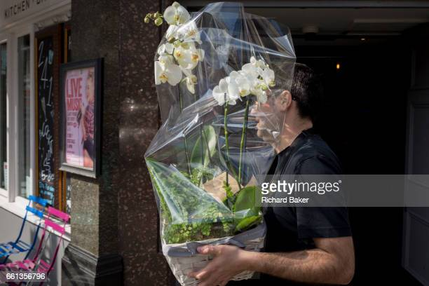 A delivery man carries an orchid through a central London street on 28th March in London England