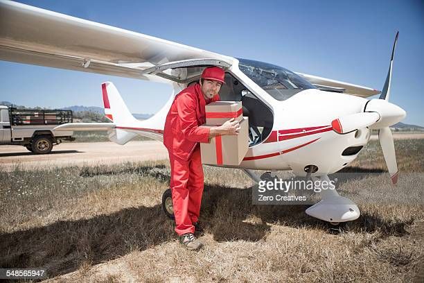 Delivery man carrying parcel off airplane, Wellington, Western Cape, South Africa