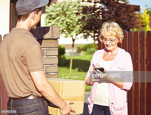 Delivery man delivering a parcel for senior woman