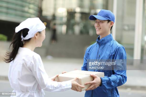 Delivery man delivering a parcel for woman