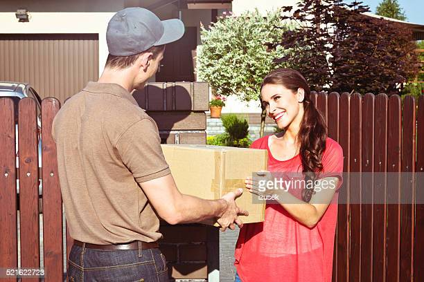 Delivery man delivering a parcel for young woman