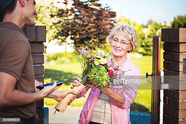 Delivery man delivering flowers for senior woman