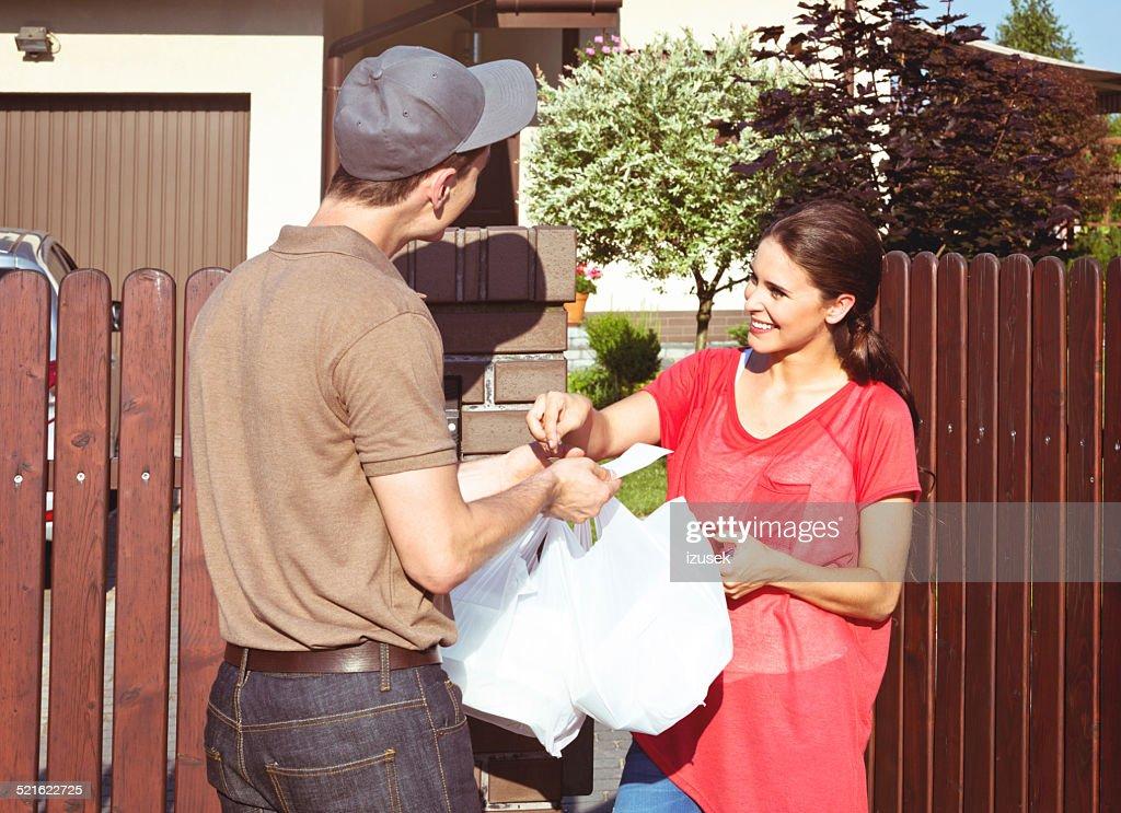 Livraison homme offrant des plats à emporter pour jeune femme : Photo
