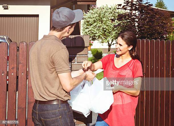 Delivery man delivering take away food for young woman